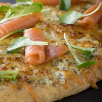 Pizza with smoked salmon, crème fraîche, herbs, garlic confit and onion compote